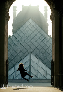 A student celebrates Bastille Day at the Louvre, jumping for joy.