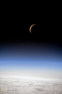Space photograph of the waning crescent moon just before it dips below the earth's horizon.